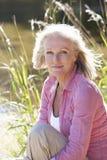 Hög kvinna som kopplar av vid sidan av sjön Arkivfoton
