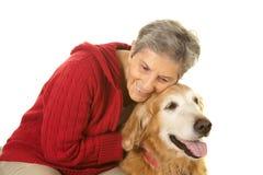 Hög kvinna som kramar hennes golden retriever Royaltyfri Fotografi
