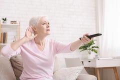 Hög kvinna som kuper hennes hand bak örat för att höra bättre arkivbilder