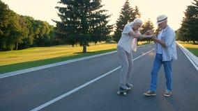Hög kvinna som lär till skateboarden med maken stock video