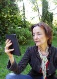 Hög kvinna som läser en eBook Royaltyfria Bilder
