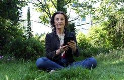 Hög kvinna som läser en eBook i trädgården Arkivbild