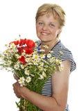 Hög kvinna som ler med gruppen av wild blommor Arkivbild