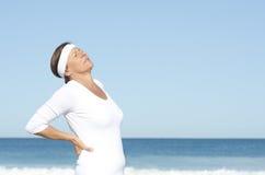 Hög kvinna som lider backpainskybakgrund Royaltyfri Foto