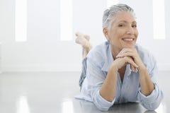 Hög kvinna som ligger på golv arkivbild