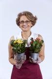 Hög kvinna som planterar blommor royaltyfria foton