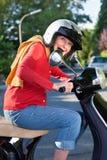 Hög kvinna som rider hennes sparkcykel Arkivbild