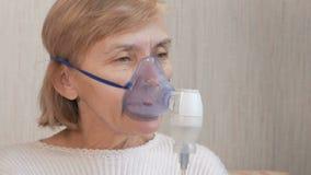 Hög kvinna som rymmer en maskering från en inhalator hemmastadd Behandlar inflammation av flygbolagen via nebulizeren Förhindra a stock video