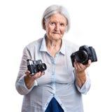 Hög kvinna som rymmer gammal analog och moderna digitala kameror i händer Royaltyfria Bilder