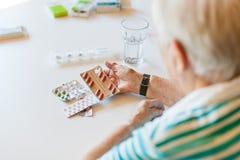 Hög kvinna som rymmer medicin och piller i hennes hand arkivbilder
