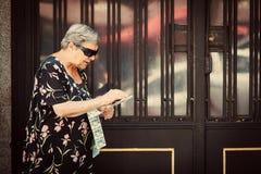 Hög kvinna som säljer lotterikuponger i gatan Arkivbild