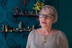 Hög kvinna som ser bort i färgrikt rum Royaltyfria Bilder