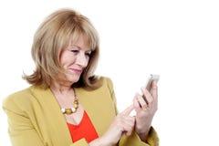 Hög kvinna som ser hennes mobiltelefon Royaltyfri Fotografi
