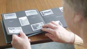 Hög kvinna som ser till och med gammalt fotografialbum lager videofilmer