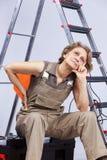 Hög kvinna som sitter i en toolbox Arkivfoto