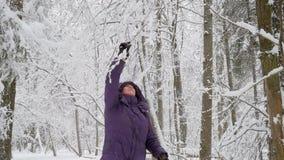 Hög kvinna som skakar av snö från filialer och att le för träd lager videofilmer