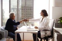 Hög kvinna som skakar händer med kvinnlig doktor In Hospital Office arkivbild