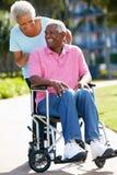 Hög kvinna som skjuter makan i rullstol Arkivfoton
