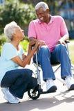 Hög kvinna som skjuter makan i rullstol Royaltyfria Foton