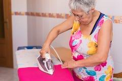 Hög kvinna som stryker kläder royaltyfri bild