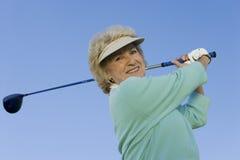 Hög kvinna som svänger en golfklubb Arkivbilder