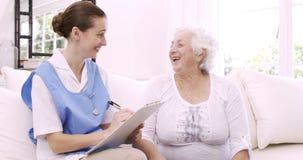 Hög kvinna som talar med sjuksköterskan