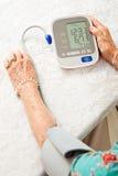 Hög kvinna som tar blodtryck royaltyfri fotografi