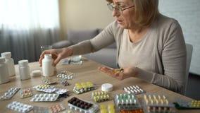 Hög kvinna som tar kapslar från alla flaskor, själv-läkarbehandling, preventivpillerböjelse arkivfilmer