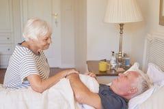 Hög kvinna som tar omsorg av hennes sjuka make i säng fotografering för bildbyråer