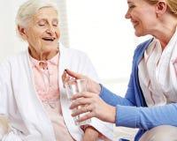 Hög kvinna som tar preventivpilleren med vatten Royaltyfria Bilder