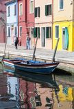 Hög kvinna som två promenerar vattenvägar med den traditionella färgrika fasaden av Burano och reflexionen Venedig arkivbilder