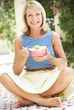 Hög kvinna som tycker om bunken av frukostsädesslag Royaltyfri Foto