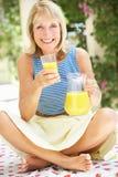 Hög kvinna som tycker om exponeringsglas av orange fruktsaft Royaltyfri Fotografi