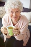 Hög kvinna som tycker om hennes te arkivfoto