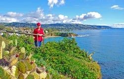 Hög kvinna som tycker om sikten på Laguna Beach, CA Royaltyfri Foto