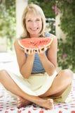 Hög kvinna som tycker om skivan av vattenmelonen Royaltyfri Fotografi