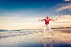 Hög kvinna som tycker om strandferiebanhoppning i luft Royaltyfria Foton