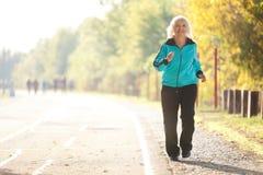 Hög kvinna som utomhus gör övningar Royaltyfri Foto