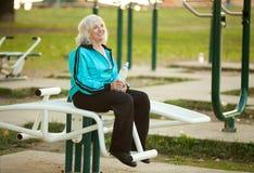 Hög kvinna som utomhus vilar efter övningar Royaltyfria Bilder