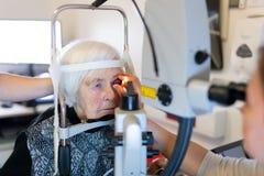 Hög kvinna under laser-kirurgi på oftalmologikliniken Fotografering för Bildbyråer