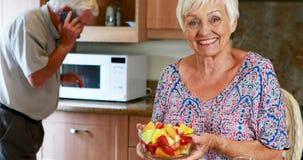 Hög kvinnainnehavbunke av frukt medan man som talar på mobiltelefonen i kök stock video