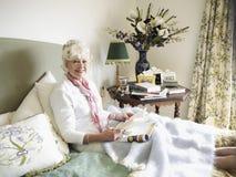 Hög kvinnaläsebok på säng Arkivfoton