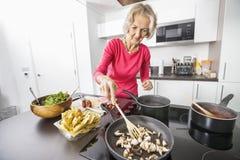 Hög kvinnamatlagningmat i kök arkivfoto