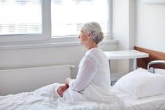 Hög kvinnapatient som ligger i säng på sjukhussalen arkivfoto