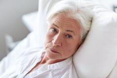 Hög kvinnapatient som ligger i säng på sjukhussalen arkivbild