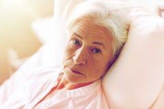 Hög kvinnapatient som ligger i säng på sjukhussalen royaltyfri bild