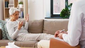 Hög kvinnapatient som talar till manpsykologen lager videofilmer