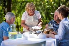 Hög kvinnaportionfrukost i trädgård Fotografering för Bildbyråer