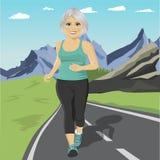 Hög kvinnaspring eller sprinta på vägen i berg Mogen kvinnlig konditionlöpare för passform under utomhus- genomkörare Arkivfoto