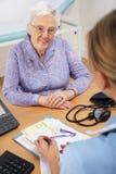 Hög kvinnatålmodig med UK-sjuksköterskan Royaltyfri Fotografi